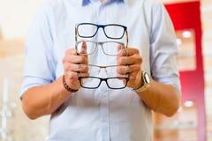 Νεαρός άνδρας στον οπτικό με τα γυαλιά Στοκ φωτογραφία με δικαίωμα ελεύθερης χρήσης