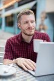 Νεαρός άνδρας στον υπαίθριο καφέ που λειτουργεί στο lap-top Στοκ Φωτογραφία