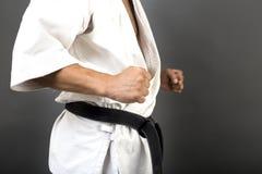 Νεαρός άνδρας στο άσπρο κιμονό και τη μαύρη πολεμική τέχνη κατάρτισης ζωνών Στοκ εικόνα με δικαίωμα ελεύθερης χρήσης