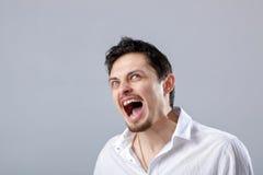 0 νεαρός άνδρας στο άσπρο πουκάμισο που κραυγάζει σε ένα γκρίζο backgroun Στοκ Φωτογραφίες