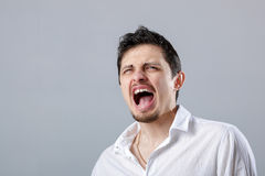 0 νεαρός άνδρας στο άσπρο πουκάμισο που κραυγάζει σε ένα γκρίζο backgroun Στοκ Φωτογραφία