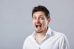 0 νεαρός άνδρας στο άσπρο πουκάμισο που κραυγάζει σε ένα γκρι Στοκ Φωτογραφία