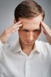 Νεαρός άνδρας στο άσπρο πουκάμισο που σκέφτεται ή που δοκιμάζει τους πονοκέφαλους Στοκ Φωτογραφίες