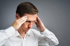 Νεαρός άνδρας στο άσπρο πουκάμισο που σκέφτεται ή που δοκιμάζει τους πονοκέφαλους Στοκ εικόνα με δικαίωμα ελεύθερης χρήσης