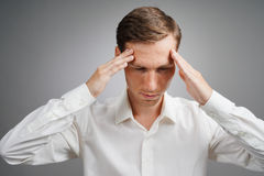 Νεαρός άνδρας στο άσπρο πουκάμισο που σκέφτεται ή που δοκιμάζει τους πονοκέφαλους Στοκ Εικόνες