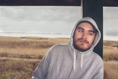 Νεαρός άνδρας στο δέλτα που φορά ένα hoodie και ένα καπέλο του μπέιζμπολ Στοκ Εικόνες