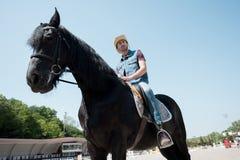 Νεαρός άνδρας στο καπέλο κάουμποϋ που οδηγά το καθαρής φυλής καφετί άλογο Στοκ φωτογραφίες με δικαίωμα ελεύθερης χρήσης