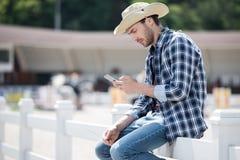 Νεαρός άνδρας στο καπέλο κάουμποϋ που χρησιμοποιεί το smartphone καθμένος στον ξύλινο φράκτη Στοκ εικόνα με δικαίωμα ελεύθερης χρήσης