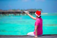 Νεαρός άνδρας στο καπέλο santa στην άσπρη παραλία με τη μικρογραφία του αεροπλάνου Στοκ φωτογραφίες με δικαίωμα ελεύθερης χρήσης