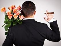 Νεαρός άνδρας στο κοστούμι με την ανθοδέσμη των τριαντάφυλλων Στοκ Εικόνα