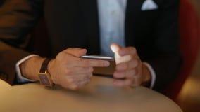 Νεαρός άνδρας στο κοστούμι που χρησιμοποιεί το smartphone φιλμ μικρού μήκους
