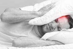 Νεαρός άνδρας στο κρεβάτι με τον ισχυρό πονοκέφαλο Στοκ Φωτογραφίες