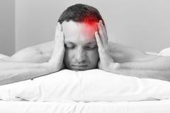 Νεαρός άνδρας στο κρεβάτι με τον πονοκέφαλο Στοκ Εικόνες