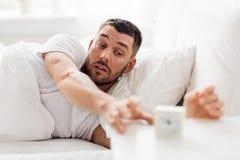 Νεαρός άνδρας στο κρεβάτι που φθάνει για το ξυπνητήρι Στοκ φωτογραφίες με δικαίωμα ελεύθερης χρήσης