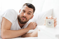 Νεαρός άνδρας στο κρεβάτι που φθάνει για το ξυπνητήρι Στοκ Εικόνες
