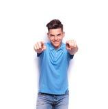 Νεαρός άνδρας στο πουκάμισο πόλο που δείχνει τα δάχτυλα Στοκ Εικόνες