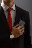 Νεαρός άνδρας στο τηλέφωνο εκμετάλλευσης κοστουμιών στο στήθος του Στοκ φωτογραφία με δικαίωμα ελεύθερης χρήσης