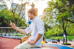 Νεαρός άνδρας στο τηλέφωνο Ντύνοντας σε ένα άσπρο πουκάμισο, μπεζ σορτς Ο νέος όμορφος επιχειρηματίας στα περιστασιακά ενδύματα κ Στοκ φωτογραφίες με δικαίωμα ελεύθερης χρήσης