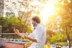 Νεαρός άνδρας στο τηλέφωνο Ντύνοντας σε ένα άσπρο πουκάμισο, μπεζ σορτς Ο νέος όμορφος επιχειρηματίας στα περιστασιακά ενδύματα κ Στοκ Φωτογραφία