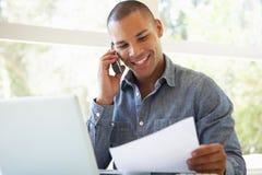Νεαρός άνδρας στο τηλέφωνο που χρησιμοποιεί το lap-top στο σπίτι Στοκ Εικόνες
