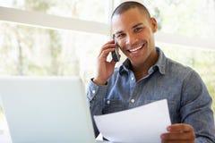 Νεαρός άνδρας στο τηλέφωνο που χρησιμοποιεί το lap-top στο σπίτι Στοκ εικόνα με δικαίωμα ελεύθερης χρήσης