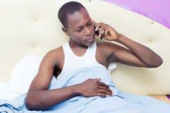 Νεαρός άνδρας στο τηλέφωνο στο κρεβάτι Στοκ Εικόνες