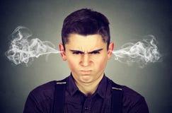 0 νεαρός άνδρας, φυσώντας ατμός που βγαίνει από τα αυτιά Στοκ Εικόνες