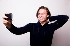 Νεαρός άνδρας χαμόγελου στο μαύρο πουλόβερ που κρατά το κινητό τηλέφωνο και που κάνει τη φωτογραφία του στοκ φωτογραφία με δικαίωμα ελεύθερης χρήσης