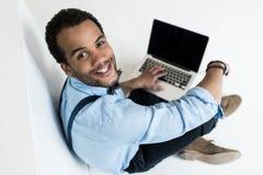 Νεαρός άνδρας χρησιμοποιώντας το lap-top με την κενή οθόνη και χαμογελώντας στη κάμερα Στοκ φωτογραφίες με δικαίωμα ελεύθερης χρήσης