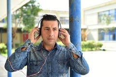 Νεαρός άνδρας χρησιμοποιώντας το smartphone και ακούοντας τη μουσική με το headp Στοκ εικόνα με δικαίωμα ελεύθερης χρήσης