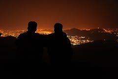Νεαρός άνδρας δύο πάνω από το λόφο που παρατηρεί την άποψη πόλεων νύχτας Στοκ Εικόνες