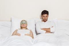 Νεαρός άνδρας Displeased με τον ύπνο γυναικών στο κρεβάτι Στοκ φωτογραφία με δικαίωμα ελεύθερης χρήσης