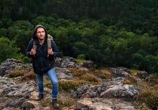 Νεαρός άνδρας Hipster με το σακίδιο πλάτης που απολαμβάνει το βουνό Ταξιδιώτης τουριστών στη δασική χλεύη άποψης υποβάθρου επάνω  Στοκ Εικόνα