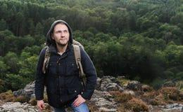 Νεαρός άνδρας Hipster με το σακίδιο πλάτης που απολαμβάνει το βουνό Ταξιδιώτης τουριστών στη δασική χλεύη άποψης υποβάθρου επάνω  Στοκ Φωτογραφία
