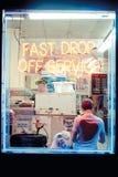 Νεαρός άνδρας Hipster σε ένα κατάστημα πλυντηρίων, που διαβάζει μπροστά από το παράθυρο σε Williamsburg Στοκ Εικόνα