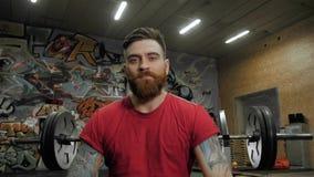 Νεαρός άνδρας weightlifter που εκπαιδεύει με τα barbells στη γυμναστική Πορτρέτο αθλητών CrossFit φιλμ μικρού μήκους