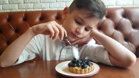 Νεαρός που τρώει το κέικ βατόμουρων φιλμ μικρού μήκους