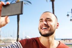 Νεαρός το άνδρας που γελά κατά λήψη ενός selfie με το κινητό τηλέφωνο Στοκ εικόνες με δικαίωμα ελεύθερης χρήσης