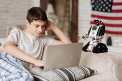 Νεαρό άτομο που κοιτάζει επίμονα στην οθόνη lap-top Στοκ Φωτογραφία