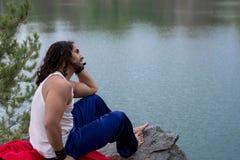 Νεαρών άνδρων έννοια τρόπου ζωής ταξιδιού καθίσματος μόνη υπαίθρια με το Λα Στοκ Εικόνα