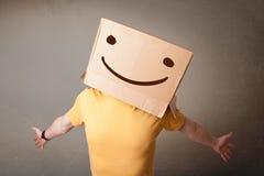 Νεαρών άνδρων με ένα κουτί από χαρτόνι στο κεφάλι του με το smiley Στοκ φωτογραφία με δικαίωμα ελεύθερης χρήσης