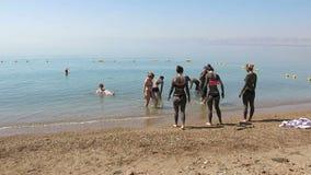 Νεκρή θάλασσα, ταξίδι της Ιορδανίας, λάσπη, κολύμβηση ανθρώπων απόθεμα βίντεο