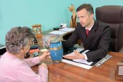 Νεκρικός διευθυντής με τη γυναίκα που εξετάζει το δοχείο στοκ φωτογραφία με δικαίωμα ελεύθερης χρήσης