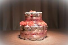 Νεογέννητη έννοια δώρων Κέικ των πανών Τυλιγμένες πάνες ως κέικ με τα λουλούδια Κέικ της τυλιγμένης καθαρής πάνας στον πίνακα με  Στοκ Φωτογραφία