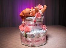 Νεογέννητη έννοια δώρων Κέικ των πανών Τυλιγμένες πάνες ως κέικ με τα λουλούδια Κέικ της τυλιγμένης καθαρής πάνας στον πίνακα με  Στοκ Εικόνα