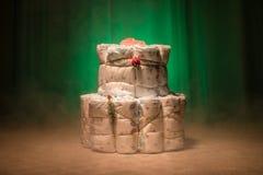 Νεογέννητη έννοια δώρων Κέικ των πανών Τυλιγμένες πάνες ως κέικ με τα λουλούδια Κέικ της τυλιγμένης καθαρής πάνας στον πίνακα με  Στοκ Εικόνες