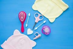 Νεογέννητη ιστορία μωρών Παιχνίδια παιδιών, ψαλίδι, μπουκάλι μωρών, θηλή, βούρτσα γηα τα μαλλιά στο μπλε υπόβαθρο στοκ φωτογραφίες