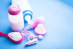 Νεογέννητη ιστορία μωρών Παιχνίδια παιδιών, ψαλίδι, μπουκάλι μωρών, θηλή, βούρτσα γηα τα μαλλιά στο μπλε υπόβαθρο στοκ φωτογραφία με δικαίωμα ελεύθερης χρήσης