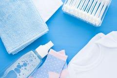 Νεογέννητη ιστορία μωρών Πετσέτες και παιχνίδια των παιδιών, ψαλίδι, μπουκάλι μωρών, θηλή, βούρτσα γηα τα μαλλιά στο μπλε υπόβαθρ στοκ εικόνα με δικαίωμα ελεύθερης χρήσης