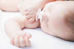 Νεογέννητος γλυκός ύπνος μωρών σε ένα άσπρο κρεβάτι με τον ειρηνιστή Στοκ Φωτογραφία